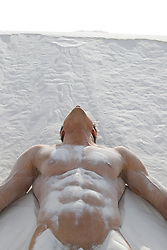 muscular man resting on a sand dune in White Sands, New Mexico