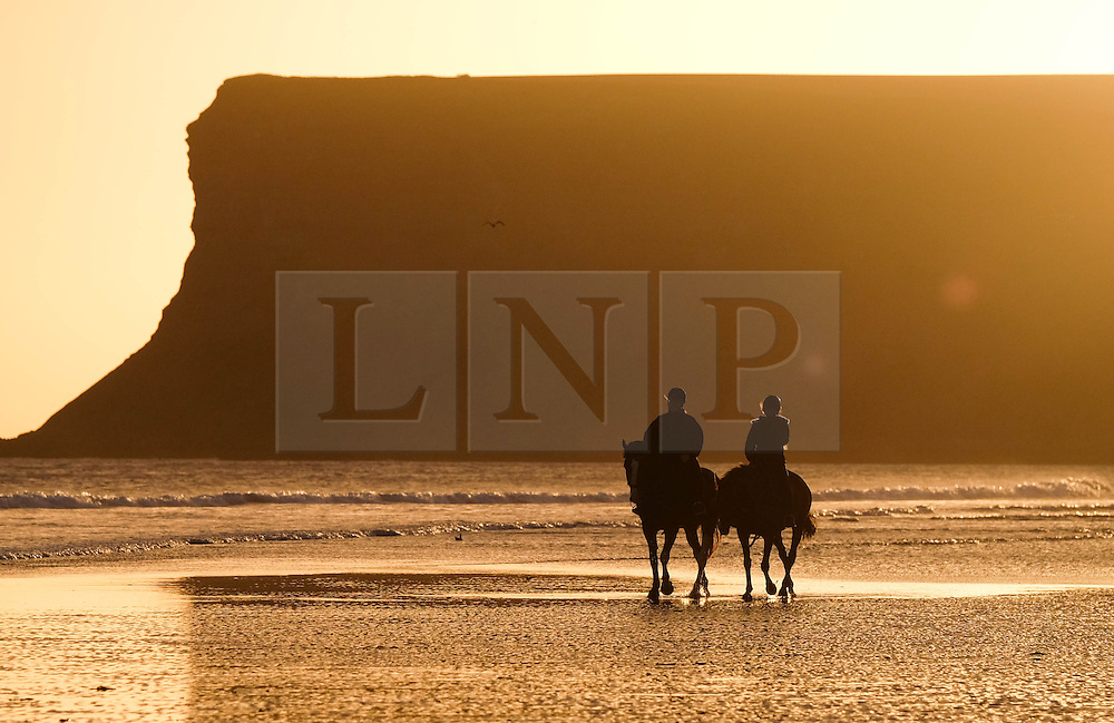 © Licensed to London News Pictures. <br /> 29/09/2016. <br /> Saltburn-by-the-Sea, UK.  <br /> <br /> Two women exercise their horses on the  beach at sunrise at Saltburn by the Sea.<br /> <br /> Photo credit: Ian Forsyth/LNP
