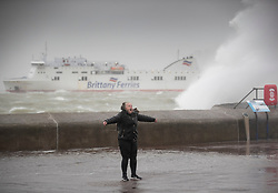 © Licensed to London News Pictures. 09/02/2020. Portsmouth, UK. A woman, soaking wet from the waves during high tide at Southsea, Portsmouth poses for a picture as a Brittany Ferry passes as Storm Ciara batters the UK. Airlines have cancelled dozens of domestic and international flights as the storm brings strong winds and rain. Photo credit: Peter Macdiarmid/LNP
