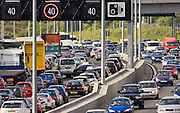 Man inspects vehicle damage after accident in traffic congestion on M25 motorway, near London, United Kingdom