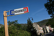 The signpost for the local Gendarmerie in blue skies, on 23rd May, 2017, in Lagrasse, Languedoc-Rousillon, south of France. Lagrasse is listed as one of Frances most beautiful villages and lies on the famous Route 20 wine route in the Basses-Corbieres region dating to the 13th century.