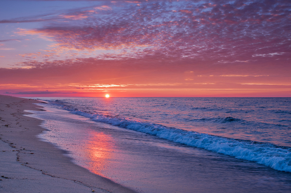 Sun sets over rolling ocean waves on beach, Cape Cod National Seashore, Provincetown, MA