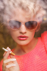 Young Woman Smoking Cigarette Behind Pane of Glass