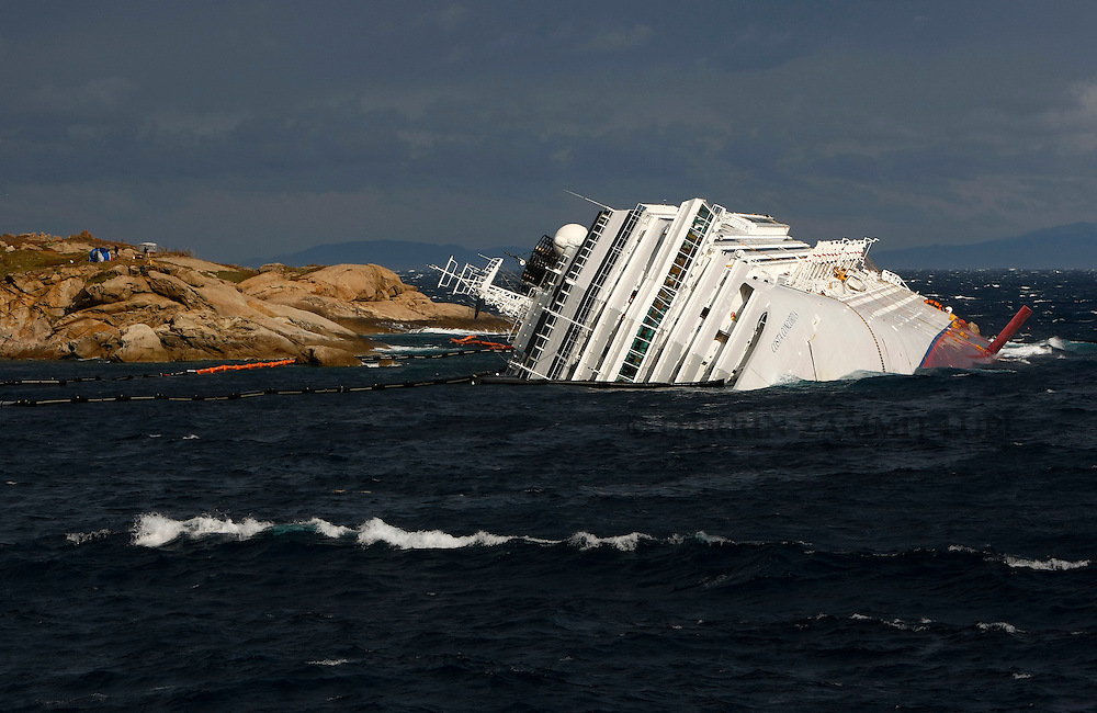 The cruise liner Costa Concordia lies on its side off the west coast of Italy at Giglio island February 1, 2012.  Rough seas and strong winds on Wednesday morning prevented rescue, salvage and anti-pollution operations from taking place in the waters off the Italian island of Giglio, where the cruise ship Costa Concordia lies capsized...REUTERS/Darrin Zammit Lupi (ITALY)