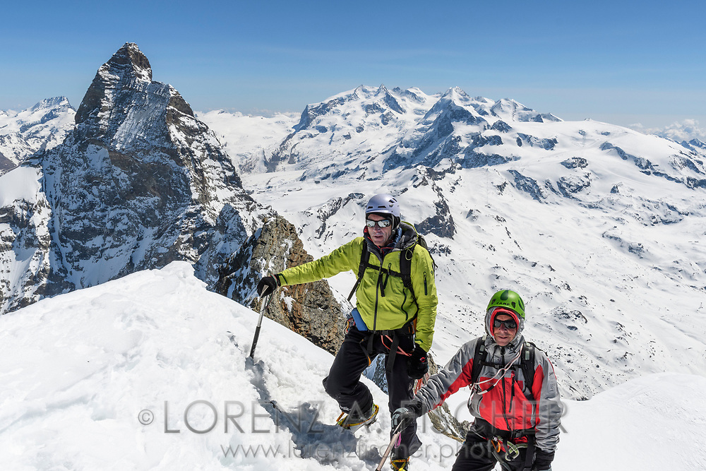 Matterhorn, Monte Rosa and two alpinists on the the peak of the Dent d'Herens, Aosta Valley, Italy
