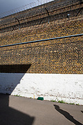 The perimeter wall guarding Her Majesty's Prison Pentonville, London, United Kingdom.  The wall is a tall brick wall and is part of the original prison complex structure. It has two layers of razor wire fence for added security.  The shadow of one of the Prison Wings is cast onto the wall and the shadow of a prisoner looking down is cast on the ground. (Photo by Andy Aitchison)