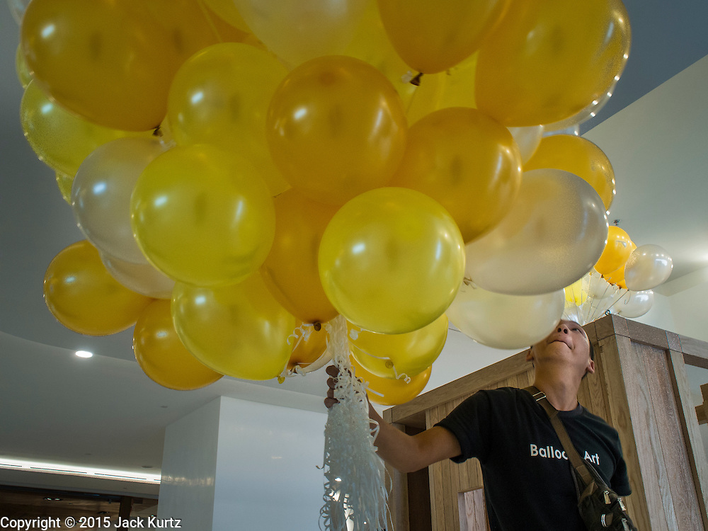 "27 MARCH 2015 - BANGKOK, THAILAND:  A worker carries balloons through ""EmQuartier,"" a new shopping mall in Bangkok. ""EmQuartier"" is across Sukhumvit Rd from Emporium. Both malls have the same corporate owner, The Mall Group, which reportedly spent 20Billion Thai Baht (about $600 million US) on the new mall and renovating the existing Emporium. EmQuartier and Emporium have about 450,000 square meters of retail, several hotels, numerous restaurants, movie theaters and the largest man made waterfall in Southeast Asia. EmQuartier celebrated its grand opening Friday, March 27.   PHOTO BY JACK KURTZ"