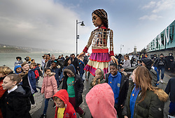 © Licensed to London News Pictures. 19/10/2021. Folkestone, UK. Local school children surround Little Amal, a giant puppet, performing on the Harbour Arm at Folkestone in Kent. The 3.5m tall puppet, worked by a team of puppeteers, has been on a journey starting from Turkey in July, visiting Greece, Italy, Switzerland, Germany, Belgium and France.  Little Amal, whose name means hope in Arabic, represents the journey of a nine year old girl from Syria. Photo credit: Peter Macdiarmid/LNP