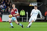 Burnley's Joey Barton (l) passes whist being challenged by Swansea's Tom Carroll. Premier league match, Swansea city v Burnley at the Liberty Stadium in Swansea, South Wales on Saturday 4th March 2017.<br /> pic by  Carl Robertson, Andrew Orchard sports photography.