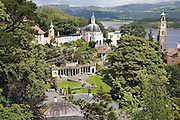 """Portmeirion, in North Wales, is a resort, where no one has ever lived. A self-taught Welsh architect named Sir Clough Williams-Ellis built it out of architectural salvage between the 1920s and 1970s, loosely based on his memories of trips to Portofino. Including a pagoda-shaped Chinoiserie gazebo, some Gothic obelisks, eucalyptus groves, a crenellated castle, a Mediterranean bell tower, a Jacobean town hall, and an Art Deco cylindrical watchtower. He kept improving Portmeirion until his death in 1978, age 94. It faces an estuary where at low tide one can walk across the sands and look out to sea. At high tide, the sea is lapping onto the shores. Every building in the village is either a shop, restaurant, hotel or self-catering accomodation. The village is booked out at high season, with numerous wedding receptions at the weekends. Very popular amongst the English and Welsh holidaymakers. Many who return to the same abode season after season. Hundreds of tourists visit every day, walking around the ornamental gardens, cobblestone paths, and shopping, eating ice-creams, or walking along the woodland and coastal paths, amongst a colourful assortment of hydrangea, rhododendrons, tree ferns and redwoods. The resort boasts two high class hotels, a la carte menus, a swimming pool, a lifesize concrete boat, topiary, pools and wishing wells. The creator describes the resort as """"a home for fallen buildings,"""" and its ragged skyline and playful narrow passageways which were meant to provide """"more fun for more people."""" It does just that.///View across Portmeirion from the Gazebo, Sir Clough Wiliams-Ellis' favorite vantage point above his creation"""