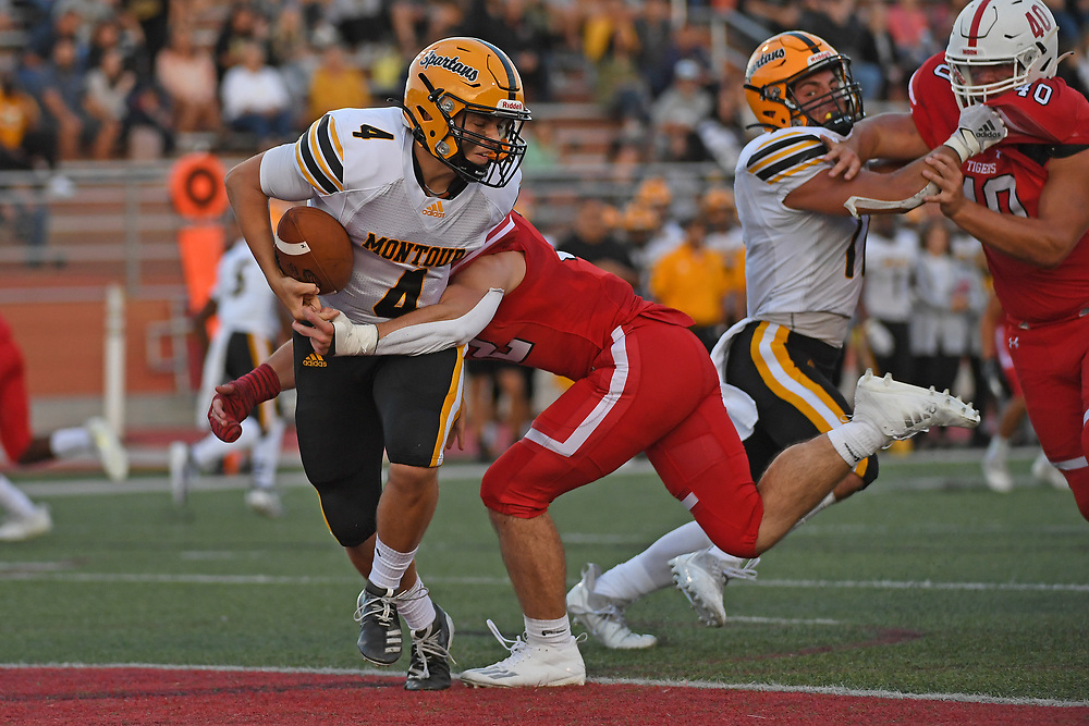 Craig Sonson Jr. #4 of the Montour Spartans is wrapped up for a sack in the end zone by Ryan Hazen #32 of the Moon Tigers in the first half during the game at Tiger Stadium on September 3, 2021 in Moon Township, Pennsylvania.
