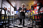 An older african-american man wears a suit and captain's hat while dancing in a restaurant in Atlanta, Georgia.