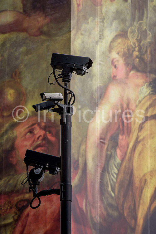 CCTV cameras keep watch on the population, seen in front of a giant construction hoarding in Whitehall, Westminster, London. With the classical figures in the background symbolising Britain's population, a society constantly under the gaze and surveillance by the state and whose data is now known to be accessed without permission for security reasons. The illustration is from the Peter Paul Rubens painting 'The Apotheosis of James I' which appears on a ceiling inside the Banqueting House, behind this screen and location of King James' son, Charles 1st execution.