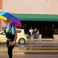 081213       Brian Leddy<br /> Ms. Gallup Pride Katrina Strom stands in the rain with her umbrella in downtown Gallup Saturday. The gay pride advocate made quite a scene, with many onlookers asking for photos.