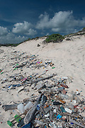 Beach trash washed up from ocean with Sand dunes in back.<br /> Playa Chiquitu<br /> Slagbaai National Park<br /> BONAIRE, Netherlands Antilles, Caribbean