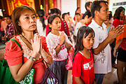 """10 FEBRUARY 2013 - BANGKOK, THAILAND:  People pray in Wat Mangkon Kamalawat, the largest Chinese temple in Bangkok, on Chinese New Year. Bangkok has a large Chinese emigrant population, most of whom settled in Thailand in the 18th and 19th centuries. Chinese, or Lunar, New Year is celebrated with fireworks and parades in Chinese communities throughout Thailand. The coming year will be the """"Year of the Snake"""" in the Chinese zodiac.   PHOTO BY JACK KURTZ"""
