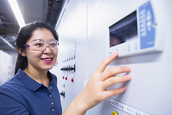 Young female engineer working at control panel in an industrial plant, Freiburg im Breisgau, Baden-Wuerttemberg, Germany