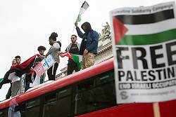 London, UK. 11th May, 2021. Pro-Palestinian demonstrators climb on top of a double-decker bus outside Downing Street as thousands of people attend an emergency rally in solidarity with the Palestinian people organised by Palestine Solidarity Campaign, Friends of Al Aqsa, Stop The War Coalition and Palestinian Forum in Britain. The rally took place in protest against Israeli air raids on Gaza, the deployment of Israeli forces against worshippers at the Al-Aqsa mosque during Ramadan and attempts to forcibly displace Palestinian families from the Sheikh Jarrah neighbourhood of East Jerusalem.