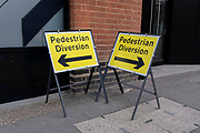 Two signs for Pedestrian Diversions point in opposite direction, their arrows and warnings causing confusion and inconsistency, on 22nd September 2021, in London, England.