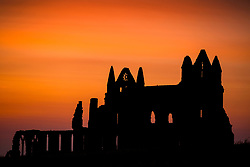© Licensed to London News Pictures. 24/06/2020. Whitby, UK. The sky turns orange after the sunset behind the gothic ruins of Whitby Abbey on the Yorkshire coast last night. Photo credit: Andrew McCaren/LNP
