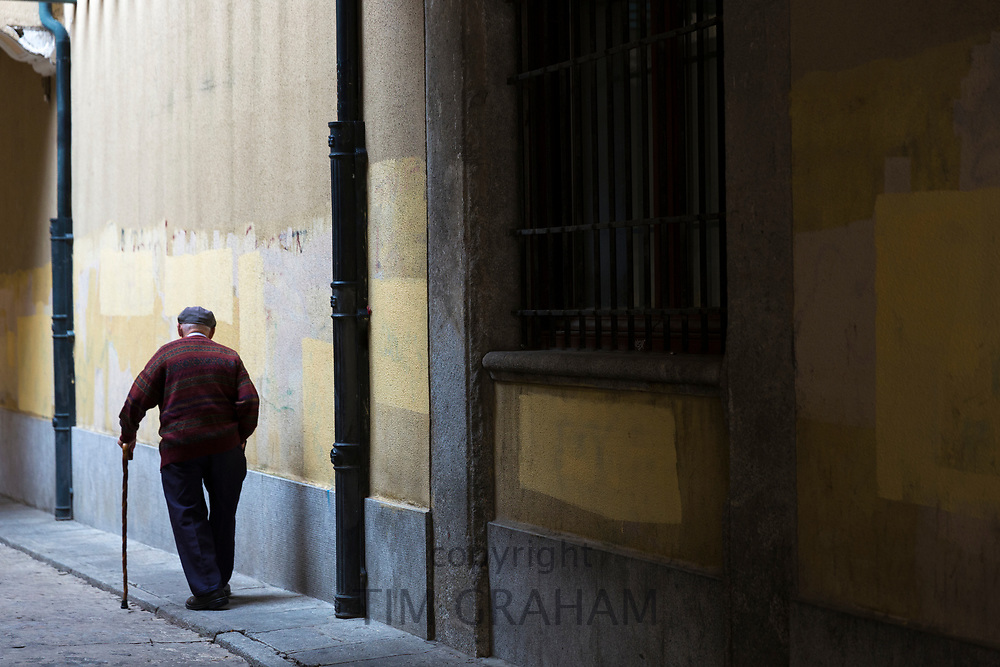 Old man with walking sick and wearing cap strolling in old town Avila, Spain