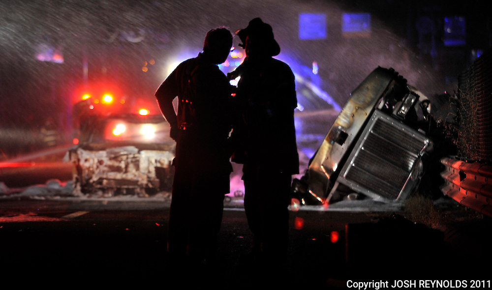 A pair of Firefighters stand beside the wreckage of a gasoline tanker that rolled over on Route 1 North in Saugus near the Square One Mall early Saturday Morning. JOSH REYNOLDS FOR THE BOSTON GLOBE (Metro, Wilson)