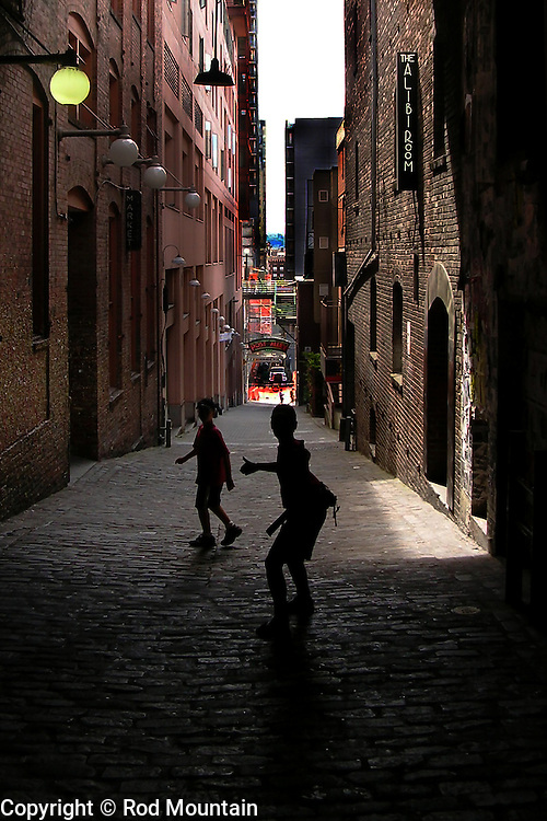Two young boys stop and turn to look back as they make their way down Post Alley in Seattle, Washington. <br /> <br /> This photo has been recognized as a Nominee in the 8th Annual International Color Awards in the professional category of Silhouette. <br /> <br /> https://www.colorawards.com/gallery/index.php?gaid=17&cid=281&x=p&g=n&fid=146262<br /> <br /> Photo: © Rod Mountain<br /> <br /> www.rodmountain.com
