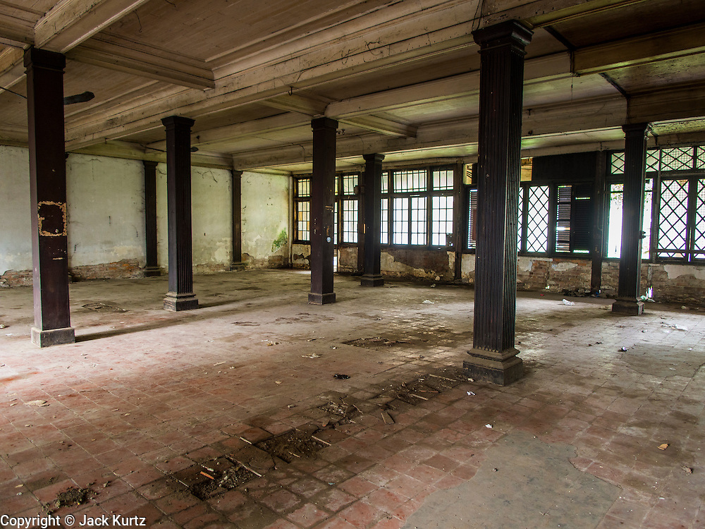 07 JUNE 2014 - YANGON, MYANMAR: A meeting room at the Pegu Club. The Pegu Club in Yangon was the Officers' Club for the British Army when Myanmar was the British colony of Burma. The club, principally made of teak, is now abandoned and in decay. Squaters have moved into the parts of the complex still standing. Yangon has the highest concentration of colonial style buildings still standing in Asia. Efforts are being made to preserve the buildings but many are in poor condition and not salvageable.    PHOTO BY JACK KURTZ
