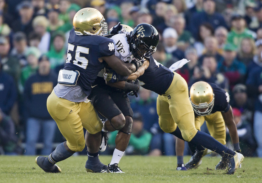 November 17, 2012:  Notre Dame safety Matthias Farley (41-right) and Notre Dame outside linebacker Prince Shembo (55-left) tackle Wake Forest running back Deandre Martin (21) during NCAA Football game action between the Notre Dame Fighting Irish and the Wake Forest Demon Deacons at Notre Dame Stadium in South Bend, Indiana.  Notre Dame defeated Wake Forest 38-0.