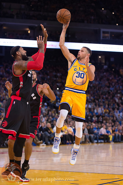 November 17, 2015; Oakland, CA, USA; Golden State Warriors guard Stephen Curry (30) shoots the basketball against Toronto Raptors forward James Johnson (3) during the third quarter at Oracle Arena. The Warriors defeated the Raptors 115-110.