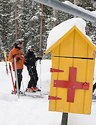 Vertical of call box with skiers at Taos Ski Valley