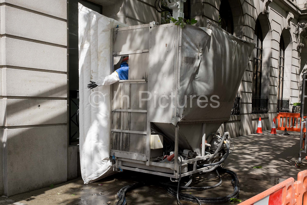 A machine operator gives a hand signal to a crane driver from inside enclosed equipment cleaning the stone work surfaces of number 1 Aldwych WC2, on 2nd May 2019, in London, England.