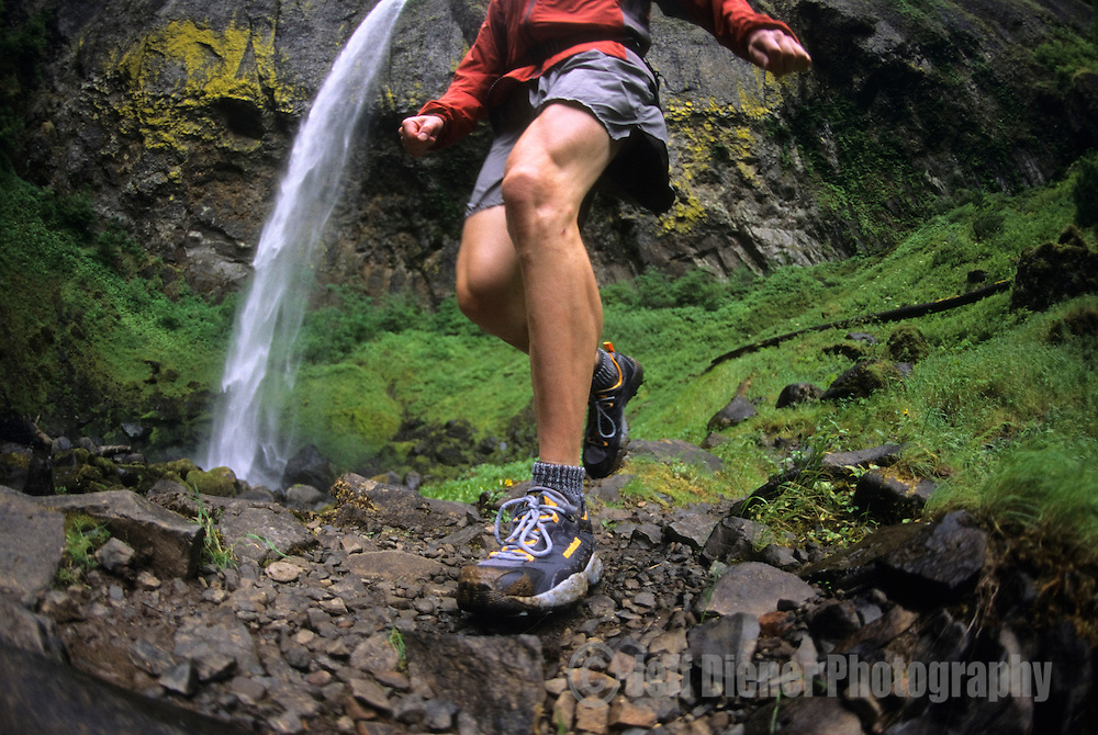 A young man runs along a rocky trail in the Columbia River Gorge, Oregon.