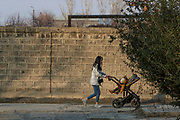 """A woman pushes a buggy-chair by the previously abandoned building of """"SOVIET Hotel"""" in Metsamor on Tuesday, Dec 28, 2020. """"SOVIET Hotel"""" is now filled with internally displaced people from Nagorno Karabakh in Metsamor. According to government statistics, there are 192 000 internally displaced people in Armenia. This figure covers displacement due to a variety of causes. However, according to IOM (International Organisation for Migration) as of Dec 2020 - an estimated 92 639 people alone were displaced as a result of military operations in areas bordering Azerbaijan due to the 44 days of war over the region of Nagorno-Karabakh. (Photo/ Vudi Xhymshiti)"""