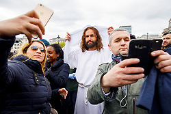 © Licensed to London News Pictures. 14/04/2017. London, UK. James Berke-Dunsmore who plays Jesus poses with members of the public taking pictures as actors of the Wintershall Players performed 'The Passion of Jesus' on Good Friday to crowds in Trafalgar Square, London on 14 April 2017. The Wintershall Players are based on the Wintershall Estate in Surrey and perform several biblical theatrical productions per year. Their production of 'The Passion of Jesus' includes a cast of 80 actors, horses, a donkey and authentic costumes of Roman soldiers in the 12th Legion of the Roman Army. Photo credit: Tolga Akmen/LNP