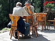 Chiesa Valmalenco (SO),località Primolo. Anziani al tavolo di uno schalet di montagna. Seniors at a table in a mountain chalet.