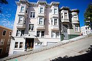 Huizen aan een steile heuvel op Kearny Street in San Francisco. In het pand is de film The Sweetest Thing opgenomen. De Amerikaanse stad San Francisco aan de westkust is een van de grootste steden in Amerika en kenmerkt zich door de steile heuvels in de stad.<br /> <br /> Houses at a steep hill in Kearny Street in San Francisco. The pink house was part of the movie The Sweetest Thing. The US city of San Francisco on the west coast is one of the largest cities in America and is characterized by the steep hills in the city.