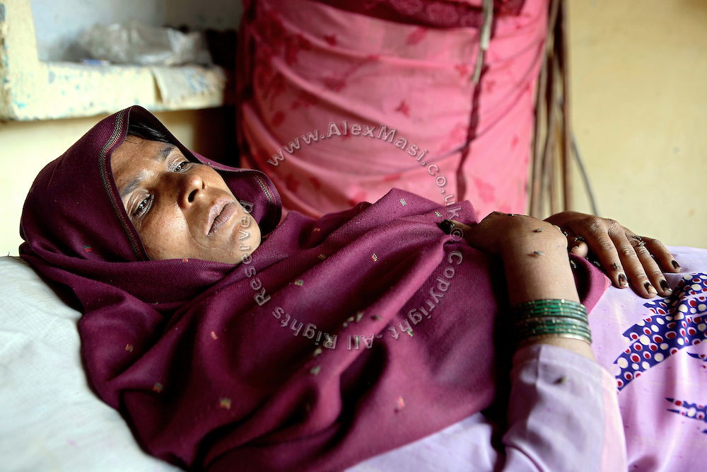 Nila Kashap, 40, from the village of Bhanera Khemchand, pop. 2000, Saharanpur District, Uttar Pradesh, India, is portrayed while resting on her bed, on Tuesday, Mar. 25, 2008. Nila started to be affected by a stomach cancer that has grown into her ovaries about one year ago and has since then incurred into 12000 Rs (USD 300) medical expenses to try and treat her disease. Doctors believe its cause to be the unsafe, yellow water she is drinking on an everyday basis from her family's private hand-pump, defined by them as being 'smelly' and 'distasteful'. Her husband, a local agricultural labourer earns as little as 50-60 Rs (USD 1) for a hard day of work in the fields and he faces regular expenses of more than 1500 Rs per month (USD 40) to try to mitigate the effects of his wife's illness. Their son, also working in the fields, is helping the family to face their dire economic situation.