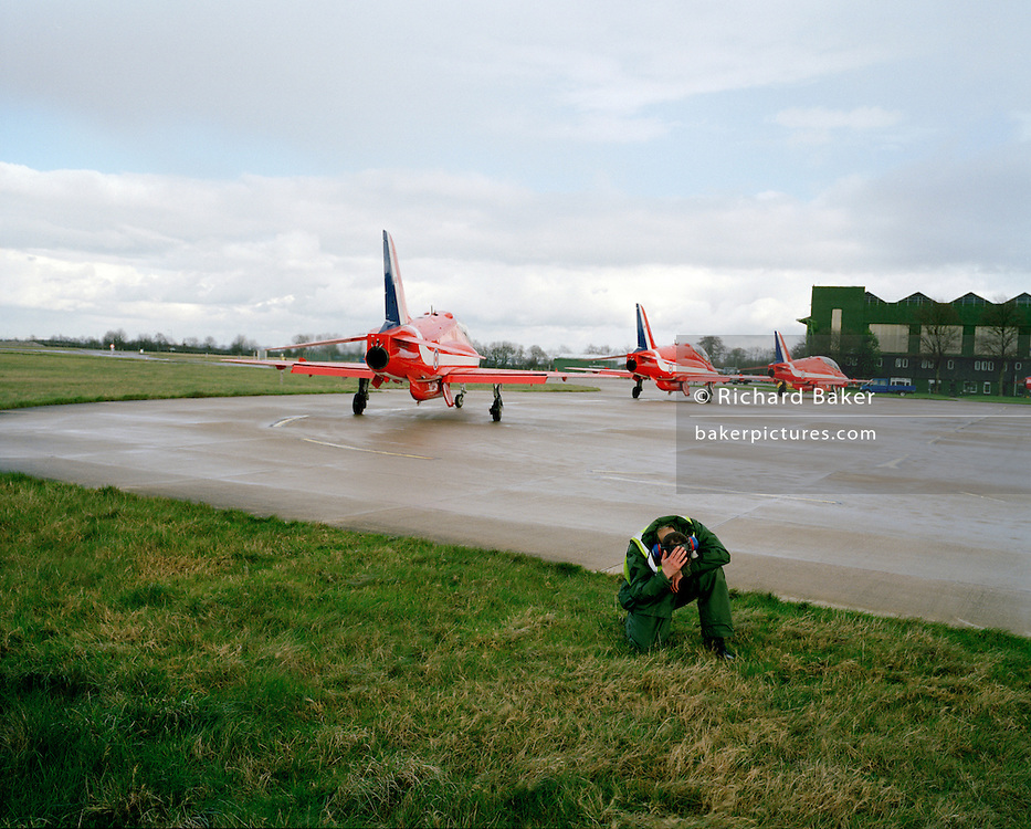 Engineering ground staff of the Red Arrows, Britain's RAF aerobatic team squats and covers head during dangerous jet blast.