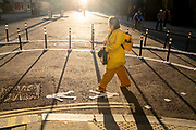 With most Londoners still working from home, a female commuter wearing yellow walks around the widened corner of Threadneedle and Old Board Streets at evening rush-hour during the third lockdown of the Coronavirus in the City of London, the capital's financial district, on 26th February 2021, in London, England.