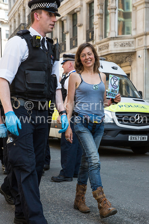 London, UK. 20th April 2019. Police officers arrest writer Jay Griffiths, a climate change campaigner from Extinction Rebellion, who had taken part in a lock-on at Oxford Circus following a policing operation to clear it of protesters earlier in the day. The heart of London's shopping district was blocked again for around two hours by the lock-ons on the sixth day of International Rebellion activities to call on the British government to take urgent action to combat climate change.