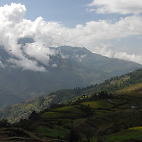 A view of hills in Nepal with partly cloudy skies.