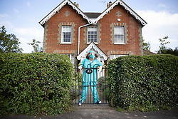 © Licensed to London News Pictures. 27/04/2020. Capel, UK. A scarecrow depiction of a doctor in hospital scrubs stands at the front of a house in the Surrey village of Capel. Residents of the village have resurrected their summer tradition of scarecrows in tribute to NHS medical staff and other key workers. Up to 30 of the life size home made doll like characters can be seen in front gardens throughout the village. The public have been told they can only leave their homes when absolutely essential, in an attempt to fight the spread of coronavirus COVID-19 disease. Photo credit: Peter Macdiarmid/LNP
