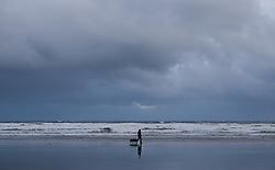 © Licensed to London News Pictures. <br /> 01/01/2017. <br /> Saltburn by the Sea, UK.  <br /> <br /> A man walks his dog along a windswept beach on New Year's Day at Saltburn.<br /> <br /> <br /> Photo credit: Ian Forsyth/LNP