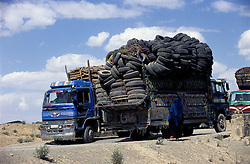 A truck transporting second-hand tyres drives towards Khost. The other two, loaded with fire woods, go to Gardez. A woman wearing a blu burka walks by.