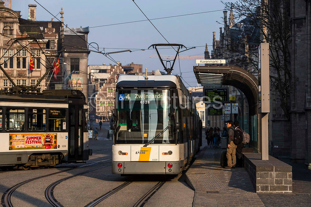 An electric tram at a station stop in the centre of Ghent city, Belgium. The Ghent tramway network is run by De Lijn.