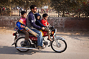 A pakistani family head for a park to play a game of cricket, Lahore, Pakistan.