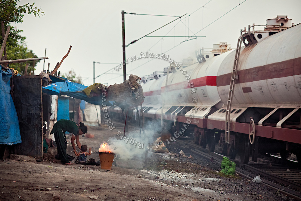 In the early morning, while a train is passing by, a boy is being picked up by his mother in front of their home along the railway tracks in New Arif Nagar, one of the water-affected colonies standing next to the abandoned Union Carbide (now DOW Chemical) industrial complex, site of the infamous 1984 gas tragedy in Bhopal, Madhya Pradesh, central India. The poisonous cloud that enveloped Bhopal left everlasting consequences that today continue to consume people's lives.