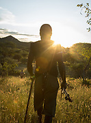 Young Hadza men hunting birds in the evening. At the Hadza camp of Dedauko.
