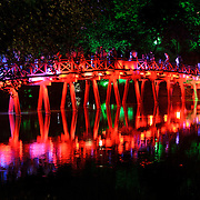 The Huc Bridge (Morning Sunlight Bridge) at night. The red-painted, wooden bridge joins the northern shore of the lake with Jade Island and the Temple of the Jade Mountain (Ngoc Son Temple).